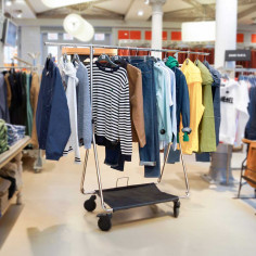 Foldable clothes rack with wheels deployed in a shop